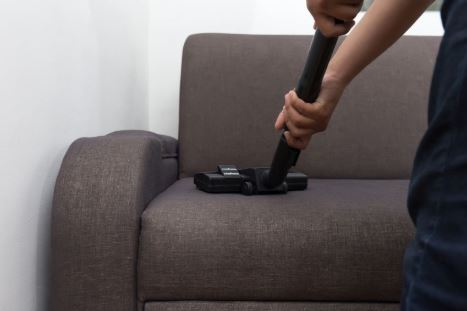 Vacuuming upholstery sofa before deep clean in Mesquite